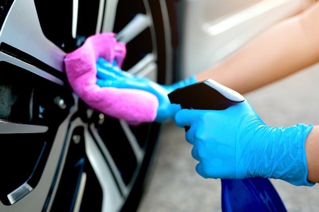 Car wheeler man in blue rubber gloves with wheel car wash cloth at car wash service