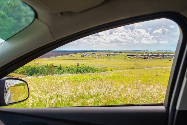 화창한 여름날 수평선에 푸른 초원과 구름이 보이는 차창