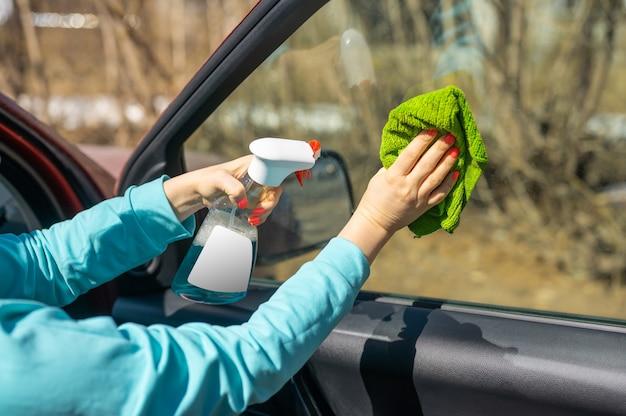 자동차 창문 청소. 여성 손 녹색 마이크로 화이버 천으로 자동차 창 청소 및 디자인에 대 한 빈 흰색 라벨 스프레이 병. 복사 공간