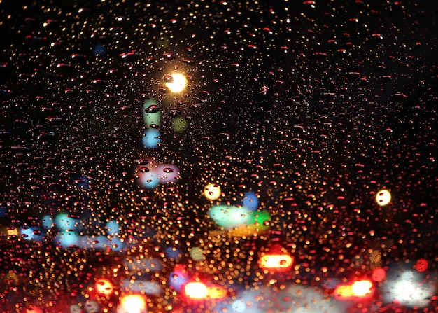 Car windshield full of raindrops with blurry traffic jam on the urban street at night