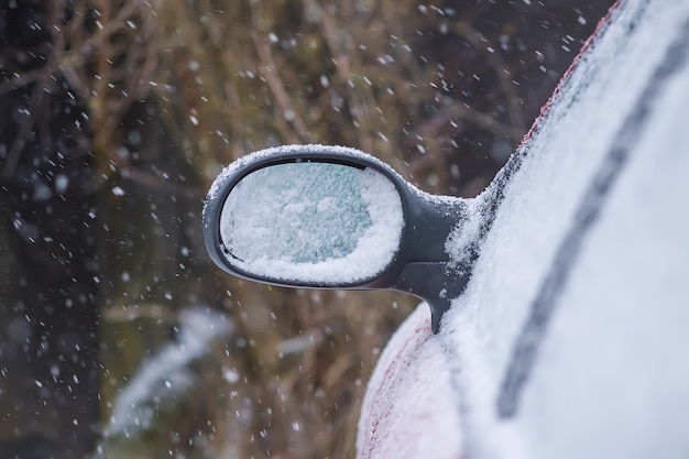 Car wing mirror covered up with fresh wet snow.