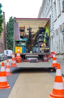 旧ヨーロッパの街の通りにある建築設備付きの車。都市工学、ヨーロッパ、道路上の建設現場