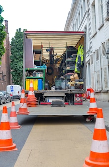 Car with building equipment on the street in old european city. urban engineering, europe, construction site on the road