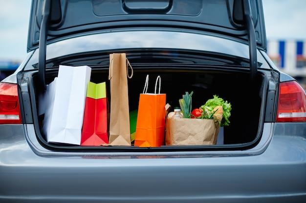 Автомобиль с картонными пакетами в открытом багажнике