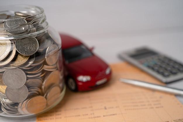 유리 항아리 자동차 대출 개념에 동전과 자동차