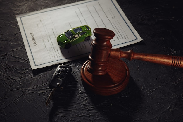 Car with keys on contract and wooden judge gavel.