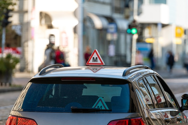 Car with latvian driving school sign on roof, defocused street with traffic lights