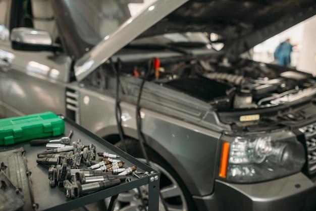 후드가 열린 자동차, 자동 서비스의 배터리 충전 프로세스, 아무도. 자동차 수리, 차량 정비