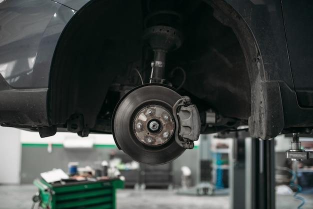 Автомобиль со снятым колесом на подъемнике, тормозной диск