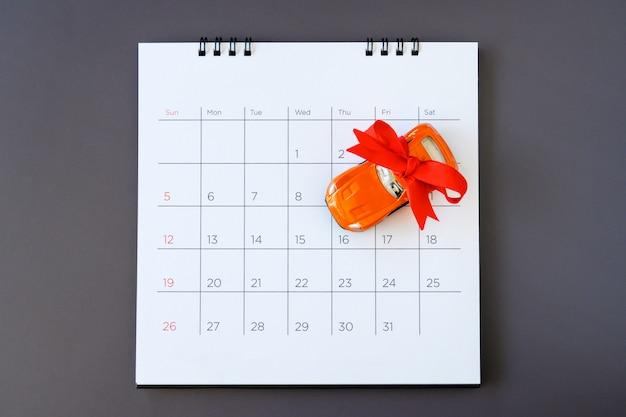 Car with ribbon on calendar, new car concept