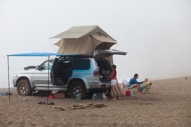 海岸にルーフテント付きの車