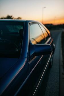 夕焼け空が窓に映る車