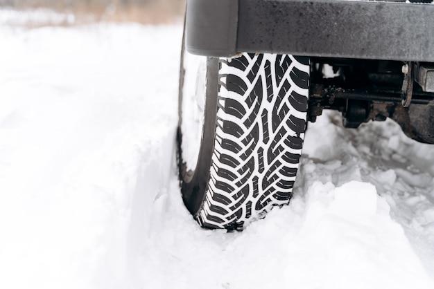 雪道、クローズアップビューで冬用タイヤを装着した車。森の中の冬の雪に覆われた道路、冬の風景に疲れる