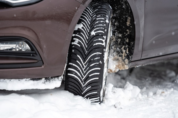 Car with winter tyres in snowy outdoors road, tire in winter on snow, close-up