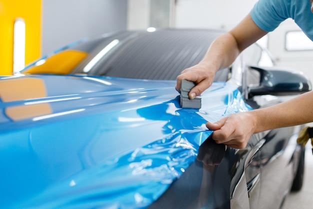 Оклейка автомобиля, слесарь с ракелем устанавливает на капот автомобиля защитную виниловую пленку или пленку. рабочий делает авто детализацию. покрытие автомобильной лакокрасочной, профессиональный тюнинг