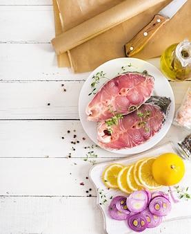 白い木製のテーブルにタイムとレモンのcar魚の生ステーキ。羊皮紙で焙煎する魚を準備します。上面図。平置き