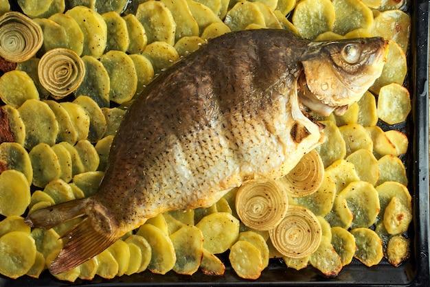 焼きcar、大皿の上にスライスしたジャガイモとオーブンからの魚全体