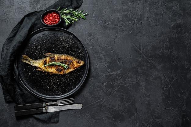 白い皿に焼きcar。川の有機魚。黒の背景。上面図。テキスト用のスペース