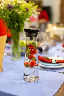 A carafe filled with water and strawberries stands on a served blue table. close up, soft focus. served table is on background in blur
