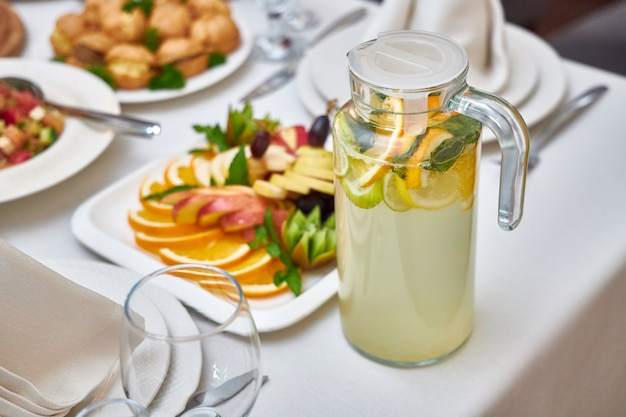 Carafe with delicious cool lemonade stands on a table in a restaurant