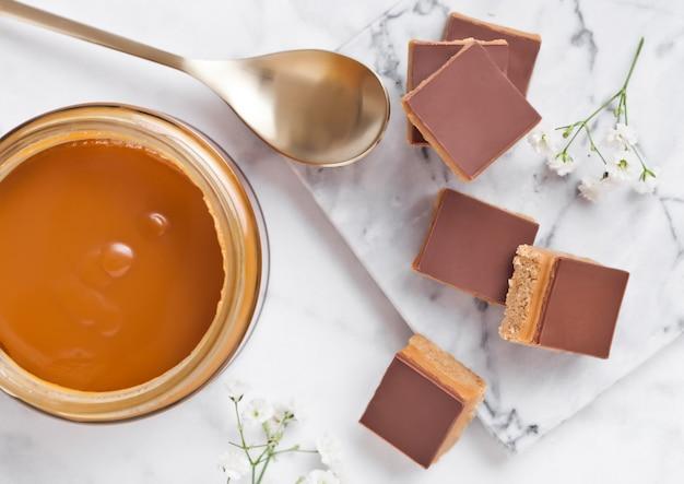キャラメルとビスケットのショートケーキは、塩味のキャラメルと金のスプーンの瓶と大理石のボードにデザートをかみます