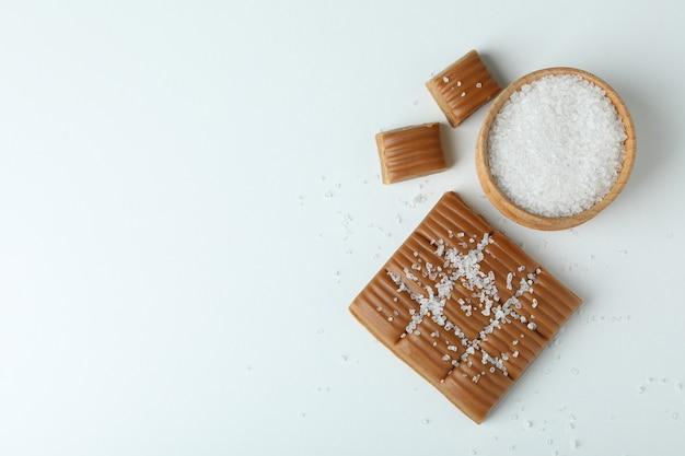 Карамель и миска соли на белом фоне