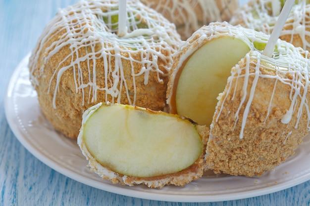 ホワイトチョコレートとグラハムのパン粉で覆われたキャラメルりんご
