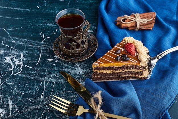 Caramel cake slice on blue surface with a glass of tea.