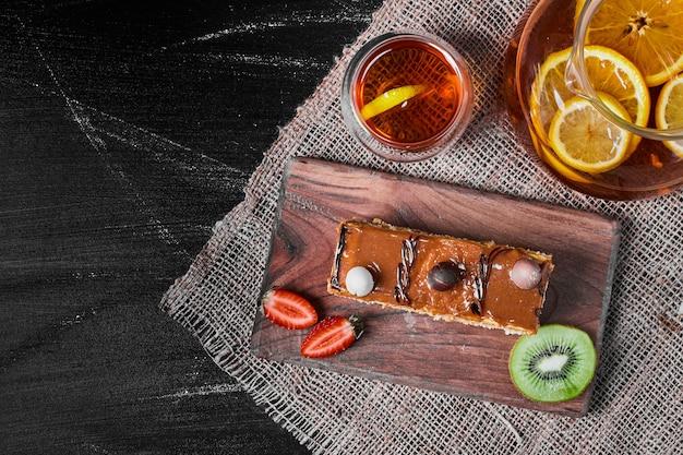 Caramel cake slice on a wooden platter .