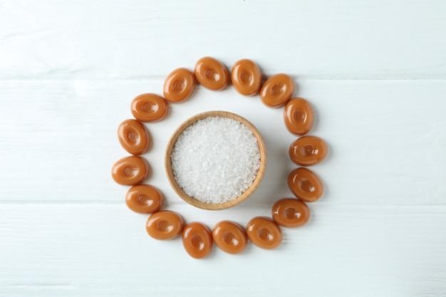 Карамельные конфеты и миска соли на белом деревянном фоне