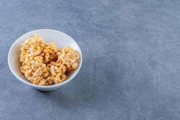 대리석 배경에 그릇에 캐러멜 사탕.