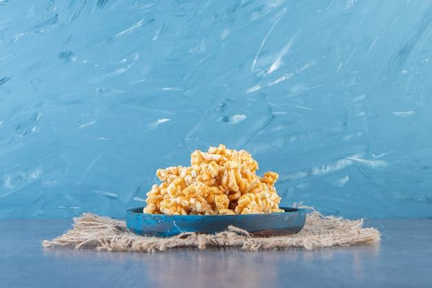 대리석 표면의 질감에 있는 나무 접시에 카라멜 사탕