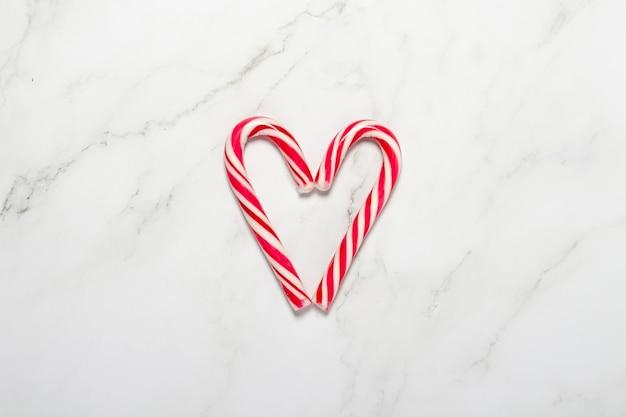 大理石の背景にハートの形に折りたたまれたキャラメルの杖。コンセプトクリスマス、新年、休日のお菓子。フラットレイ、上面図。