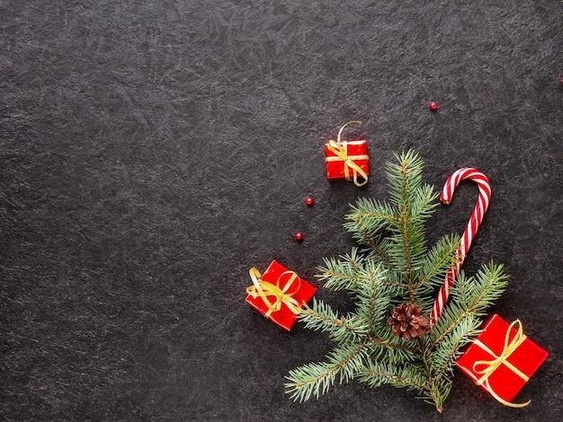 나뭇가지가 있는 캐러멜 지팡이는 어두운 배경에 구슬과 크리스마스 트리 장난감을 부딪칩니다.