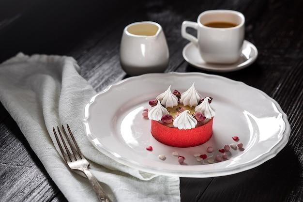 Карамельный чизкейк со сливками и цветами на деревянных фоне. чашка кофе и торт на белой тарелке