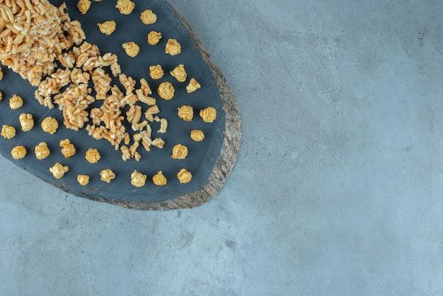 Disposizione dello spuntino rivestito del caramello su una tavola di legno sulla superficie di marmo