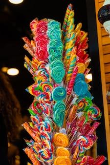Caramel colored lollipops for children on sticks at entrance to market