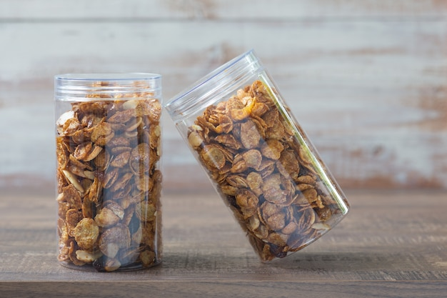 Caramel cornflakes in plastic jar package on wooden table.
