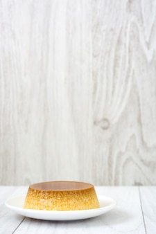 Caramel custard dessert on white dish with wooden surface.