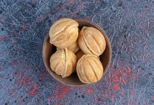 キャラメルは抽象的なテーブルのボウルにクッキーボールを満たしました。