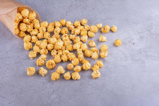 Попкорн со вкусом карамели, высыпанный из бумажной упаковки на мраморном фоне. фото высокого качества