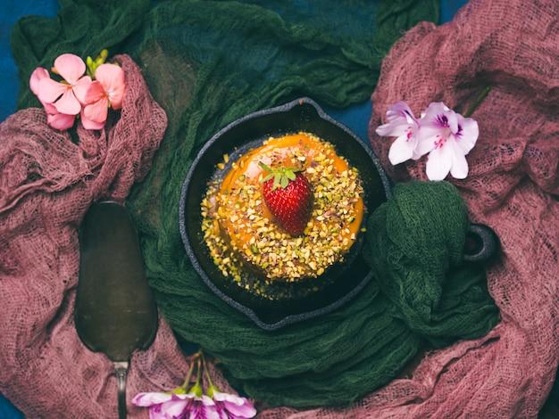 Карамельный глазированный торт с клубничным цветочным декором на темном фоне с текстилем. осенний зимний десерт натюрморт