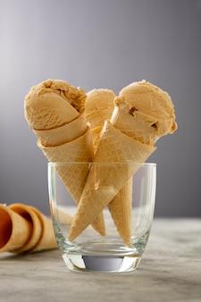 카라멜 아이스크림은 건포도와 함께 어두운 배경의 와플 콘에 삽니다. 맛있는 여름 아이스크림 치료.