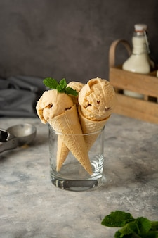 Caramel ice cream scoops with raisins, in a waffle cones on dark background. delicious summer ice-cream treat.