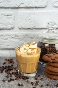 Caramel latte coffee in a glass with whipped cream and chocolate cookie. coffee beans on gray and white brick wall surface with copy space.