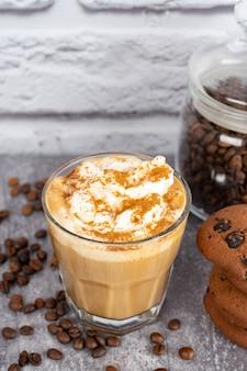 Карамельный кофе латте в стакане со взбитыми сливками и шоколадным печеньем. кофейные зерна на серой и белой поверхности кирпичной стены с космосом экземпляра.