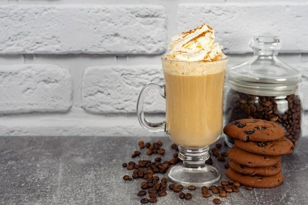 Карамельный кофе латте в высоком стакане со взбитыми сливками и шоколадным печеньем. кофейные зерна на серой и белой поверхности кирпичной стены с космосом экземпляра.