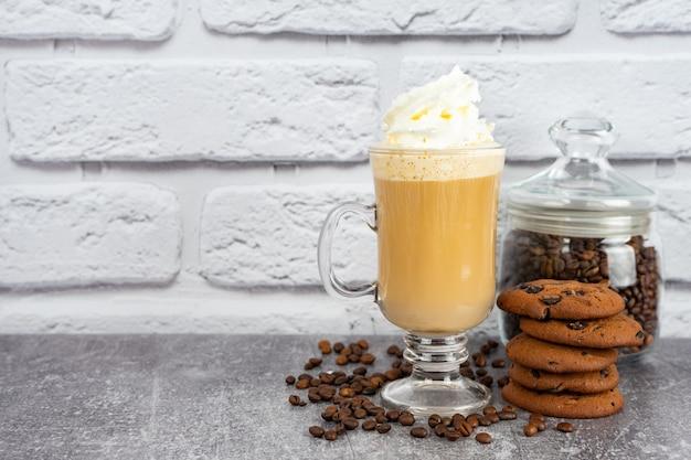 Карамельный кофе латте в высоком стакане со взбитыми сливками и шоколадным печеньем.