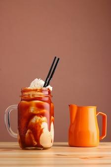 Карамельный молочный коктейль с кофе на деревянном столе