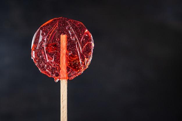 スティックロリポップのキャラメルベリーとフルーツの甘いデザートピース手作りの新鮮な部分
